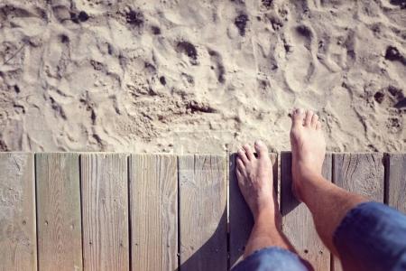 Photo pour Homme aux pieds nus sauter promenade sur la plage de sable - image libre de droit