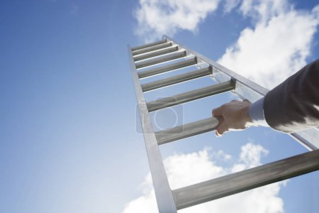 Businessman climbing Ladder of success