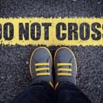 Do not cross line child in sneakers standing next ...