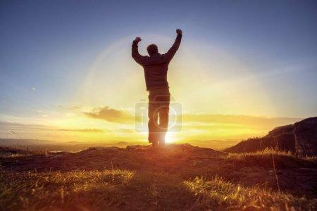 Photo pour Homme heureux célébrant le succès gagnant ou culte et louange contre le coucher du soleil - image libre de droit