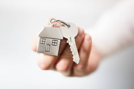 Photo for Holding house keys on house shaped keychain concept for buying a new home - Royalty Free Image