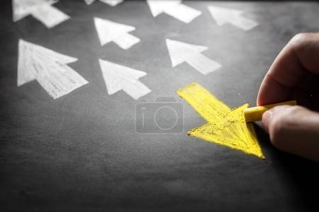 Photo for Individuality chalk arrow going a different direction on blackboard - Royalty Free Image