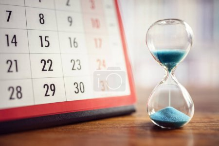 Photo for Hour glass and calendar concept for time slipping away for important appointment date, schedule and deadline - Royalty Free Image