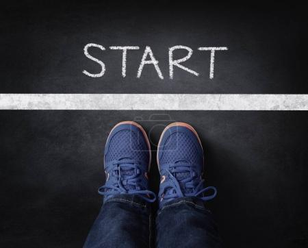 Photo for Start line child in sneakers standing next to chalk starting line on blackboard - Royalty Free Image