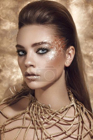 Beauty Fashion model girl with Golden Makeup, on golden background.