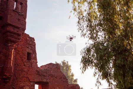 Photo pour Drone avec la caméra professionnelle prend des photos au-dessus des ruines antiques. Hexacopter drone avec caméra numérique haute résolution sur le ciel - image libre de droit