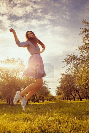 happy girl jumping in sunny day in summer garden