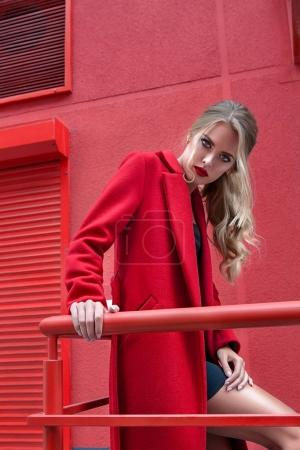 Photo for Fashion portrait stylish woman in red coat over red urban background - Royalty Free Image