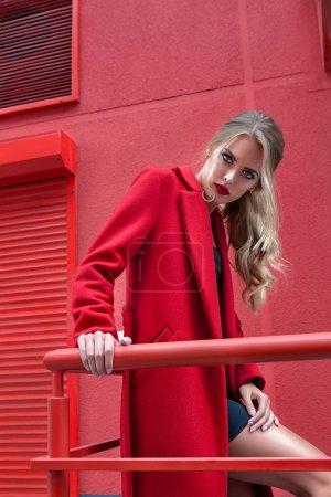 Photo pour Mode portrait élégante femme en manteau rouge sur fond rouge - image libre de droit
