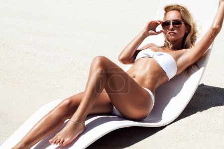 fashion photo of beautiful tanned woman with blond hair in elegant white bikini relaxing on white chair