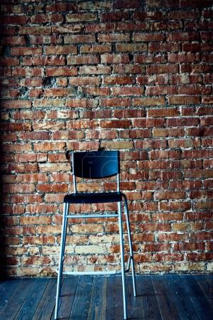 Photo for Black modern chair on brick wall background. - Royalty Free Image