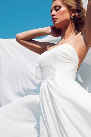 Beautiful bride with fashion wedding hairstyle - on sky background.
