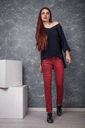 Photo for Full Length Portrait of Trendy Hipster Girl Standing at the Gray Wall Background. Urban Fashion Concept - Royalty Free Image