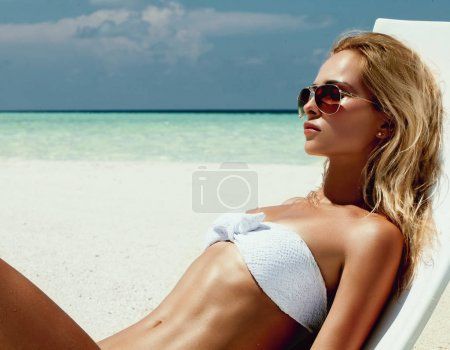 Photo for Summer girl model with tanned sexy body. Posing in the white chair on the beach of the tropical island. - Royalty Free Image