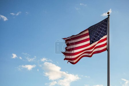 Photo for American flag blowing in the wind on the blue sky. - Royalty Free Image