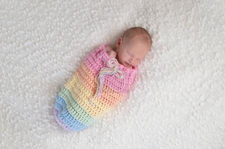 Bebé recién nacido en una bolsa de color arco iris