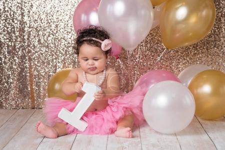 Photo pour Une fille âgée d'une an, Bébée jouant avec un grand bloc sous la forme d'un nombre. Elle est vêtue d'un tutu rose, serre-tête fleur et un collier de perles. - image libre de droit