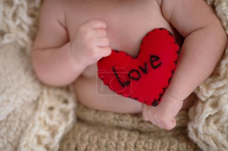 """Photo for Six week old baby holding a little, red pillow with the word, """"Love"""" written on it. - Royalty Free Image"""