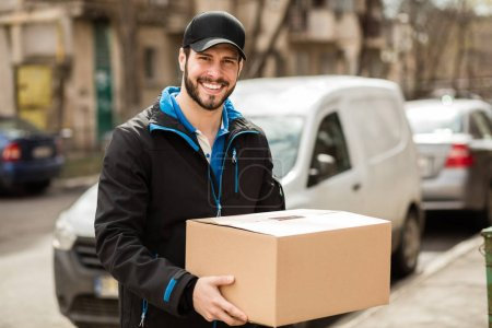 Photo for Delivery man with cap and cardboard in hands - Royalty Free Image
