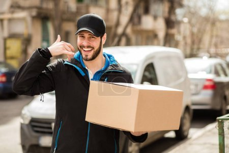 Photo pour Livreur avec capuchon et carton dans les mains, faire un signe phonecall avec la main - image libre de droit