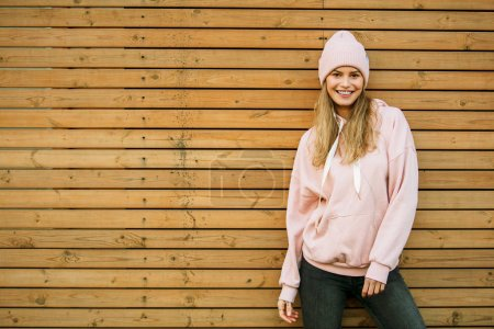 Photo for Cool hipster young woman in pink hoodie and pink fur cap standing on wooden background - Royalty Free Image