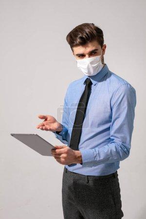Photo pour Élégant homme d'affaires ou des choses médicales, travaillant sur une tablette avec masque facial pour virus contagieux - image libre de droit