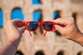 Closeup sunglasses in hands in front of Colosseum in Rome, Italy