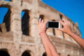 Tourist taking a picture by smartphone of Great Colosseum, Rome, Italy