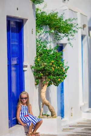 Adorable girl having fun outdoors. Kid at street of typical greek traditional village with blue door on greek island