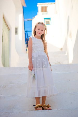 Adorable girl outdoors in greek village. Kid at street of typical greek traditional village with white stairs on greek island