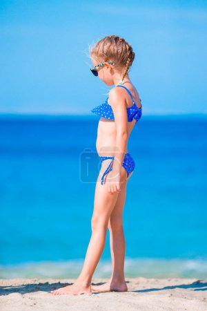 Adorable little girl in swimsuit on beach vacation
