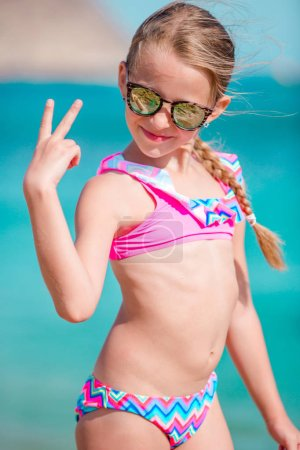Photo for Adorable smiling little girl on beach tropics vacation - Royalty Free Image