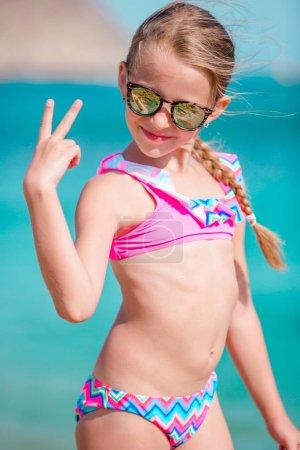 Photo pour Adorable petite fille souriante sur la plage tropiques vacances - image libre de droit