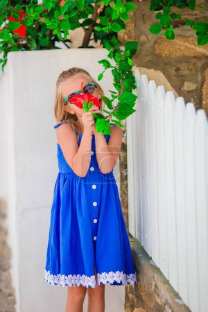 Little adorable girl smelling colorful flowers outdoors on greek streets