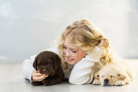cute little girl in white woolen sweater lying on floor with adorable puppies