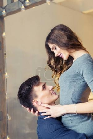 young man lifting his girlfriend up standing in room with Christmas lights