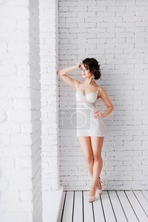 young brunette woman in white dress posing on white brick background