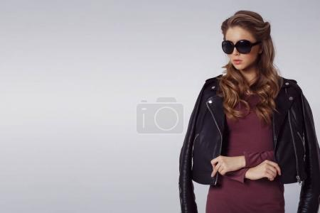fashion portrait of young beautiful woman wearing stylish clothes over grey background