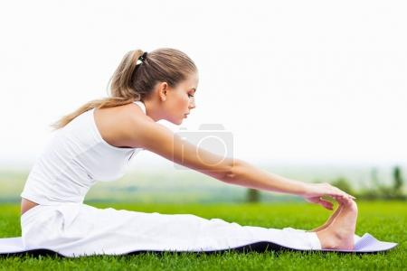 portrait of young slim woman doing stretching exercise on yoga mat outdoor, healthy lifestyle, yoga and sport concept