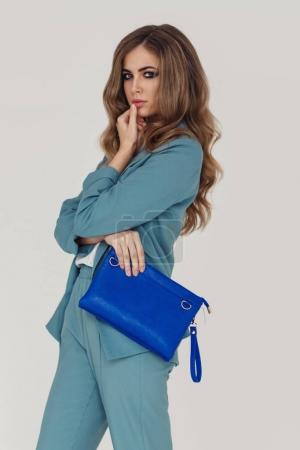 Photo for Fashion portrait of young beautiful woman wearing blue suit and holding purse - Royalty Free Image