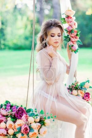 fashion portrait of young beautiful woman in romantic dress posing on swing decorated with flowers outdoor