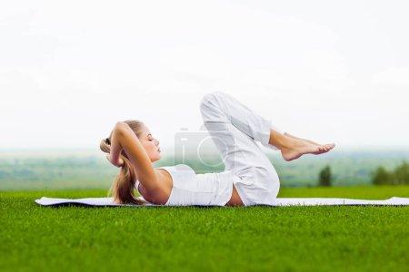 Photo pour Portrait de jeune femme mince faisant des exercices d'étirement sur tapis de yoga en plein air, mode de vie sain, yoga et sport concept - image libre de droit