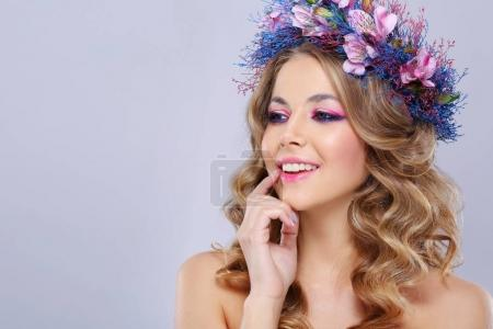 portrait of young beautiful woman wearing wreath of pink and blue flowers posing over grey background