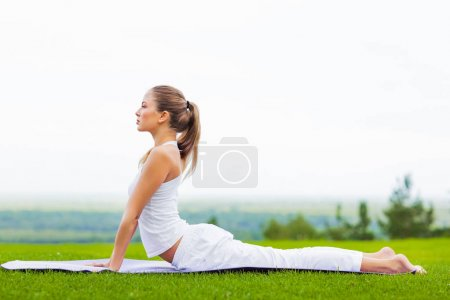 Photo for Portrait of young slim woman exercising on yoga mat outdoor, healthy lifestyle, yoga and sport concept - Royalty Free Image