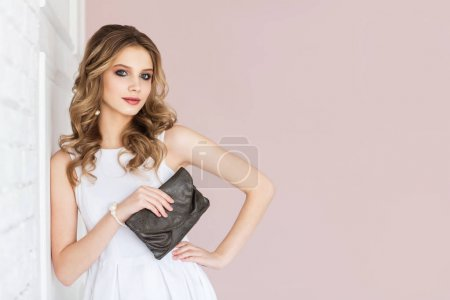 Portrait of young blonde woman with wavy hair wearing white dress and holding dark clutch posing at camera
