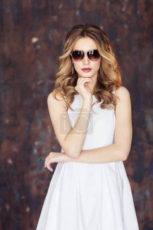 Young blonde woman wearing white dress, beige high-heeled and sunglasses posing at camera