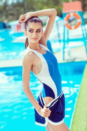 Photo for Attractive brunette girl posing in stylish blue and white swimsuit near swimming pool - Royalty Free Image