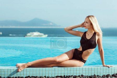 Photo for Young model girl in black bikini posing near pool - Royalty Free Image