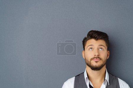 Thoughtful man standing against dark background