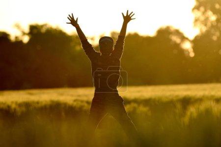 Photo pour Little Boy Freedom saute dans un champ de blé au coucher du soleil, France - image libre de droit